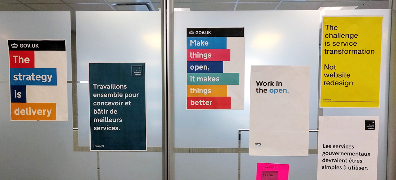 "Posters on the wall of a government office, saying: ""The strategy is delivery,"" ""Travaillons ensemble pour concevoir et bâtir de meilleurs services,"" ""Make things open, it makes things better,"" and other catchphrases."